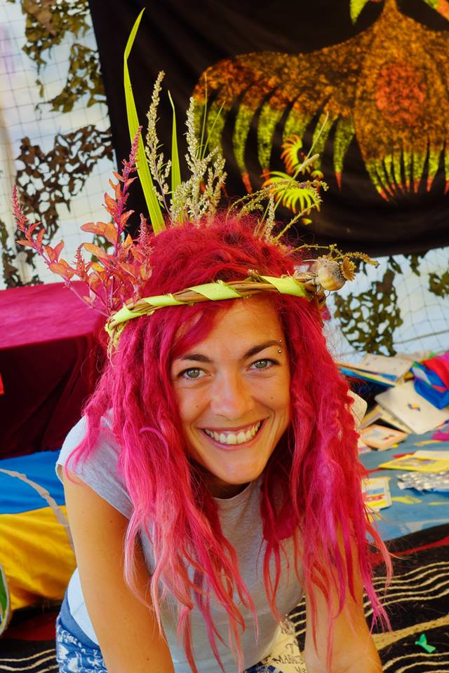 Smiling woman with pink hair and head-dress