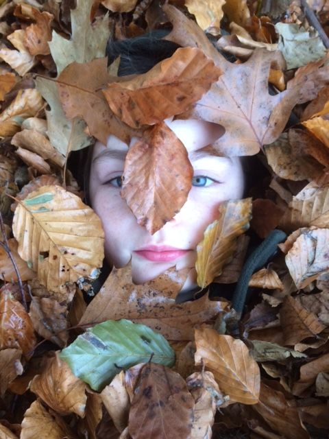 child's face in autumn leaves