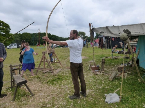 Man holding handmade wooden bow